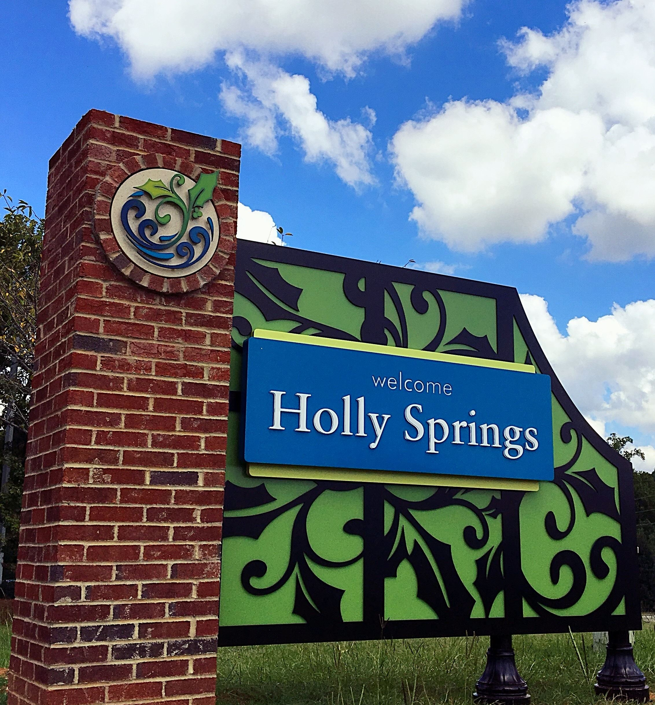 large road sign that says welcome Holly Springs